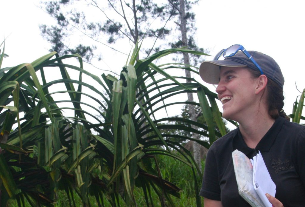 Rachel holding a notebook and laughing with tropical foliage in the background.